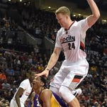 Los Angeles Lakers forward Kobe Bryant (24) reaches in on Portland Trail Blazers center Mason Plumlee (24) during the first half of an NBA basketball game in Portland, Ore., Saturday, Jan. 23, 2016.