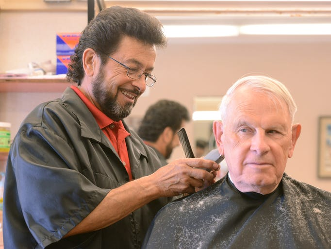 Kenny Cordova, left, owner of Frank's Lemay Center Barbershop, cuts the hair of Bill Woods of Fort Collins Wednesday morning June 11, 2014.