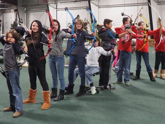 A group of students pose for a photo with their bows