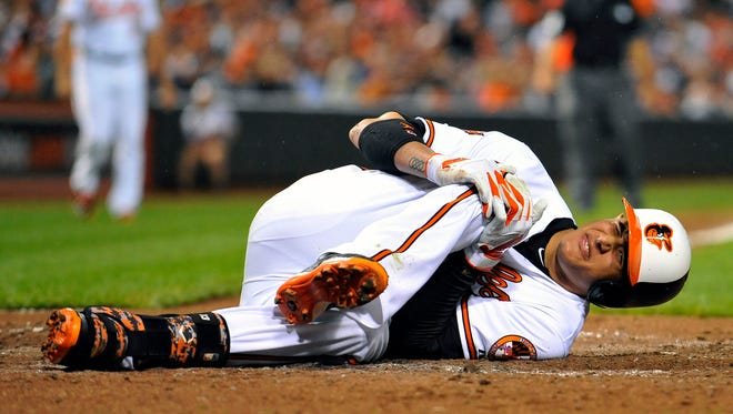 Manny Machado goes down with a knee injury after striking out in the third inning of Monday's game.