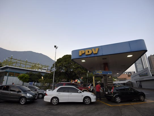 Cars wait in lines at a gas station in Caracas on Feb.17,
