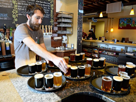 Johnny Daggett prepares beer flights for a tour group