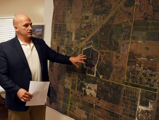 Port St. Lucie Mayor Greg Oravec describes the flow of water on a newly proposed water farm on an overview map of the McCarty Ranch Preserve on Tuesday, Dec. 20, 2016.