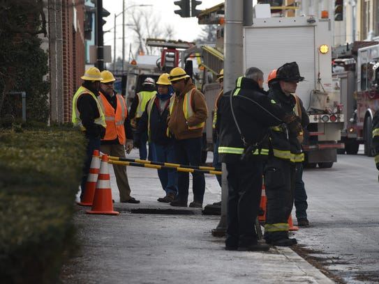 Firefighters and workers stand on Catharine Street