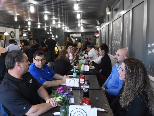 Patrons sit for a meal at Lola's Cafe in the City of