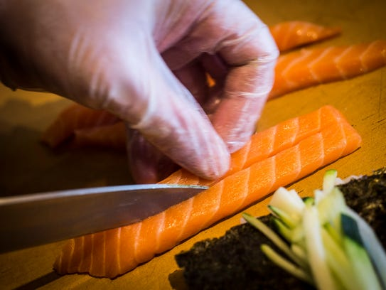 Salmon is prepared for a Dragon Roll at Asian Bistro