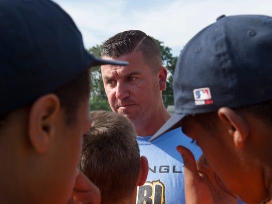 Coach Brandon Mattingly gathers his team between innings