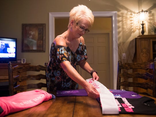 Debbie Pearsall lays out a breast cancer survivor sash