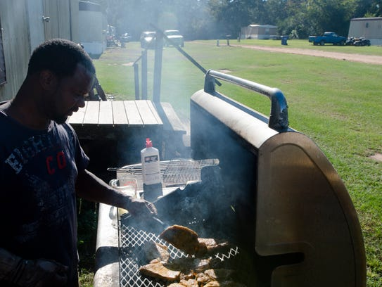 Lorenzo June grills pork chops outside his trailer