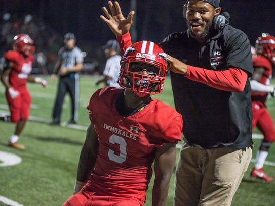 Shedro Louis celebrates after a touchdown with coach
