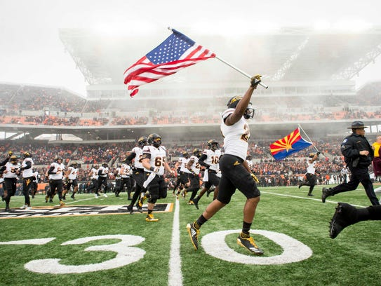 Arizona State's Chad Adams runs with an American flag