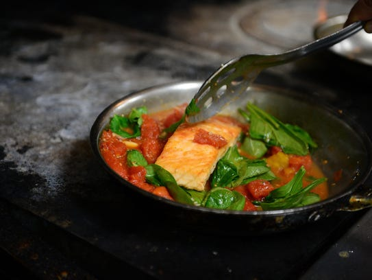 Vinny Bellia prepares his grilled salmon over hot spinach