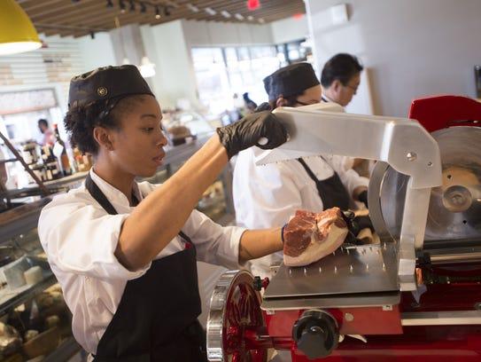 Donita Brown slices a cut of ham at the deli counter