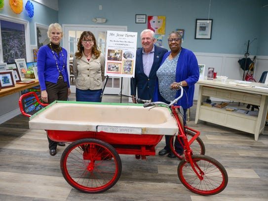 Laura Allen, town administrator, Ivy Wells, Economic and Community Development director, Berlin Mayor Gee Williams and Cassandra Brown, volunteer, stand with the donated bathtub racer of Jesse Turner. That can now be seen at Berlin's Welcome Center on Main Street.