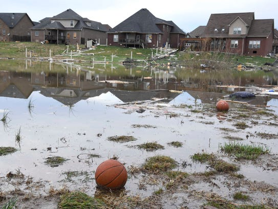 Basketballs rest in water surrounded by debris Feb.