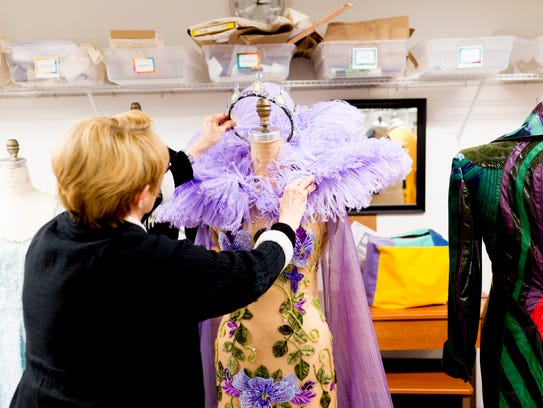 """Marianne Custer puts a tiara on a costume from a past production of """"A Midsummer Night's Dream"""" at the Clarence Brown Theatre costume shop in Knoxville on April 11. The play is among the dozens she's designed costumes for at the University of Tennessee theater."""
