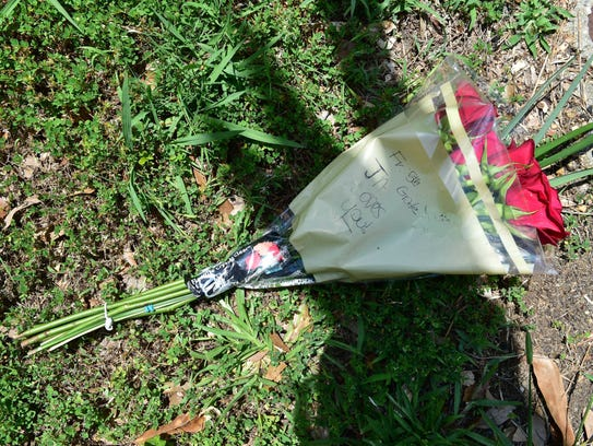 Flowers were left across the street for the site of