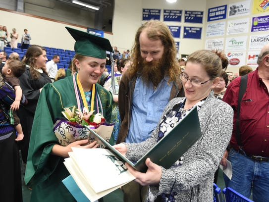 Emma Flora admires her diploma with her sister Rachael