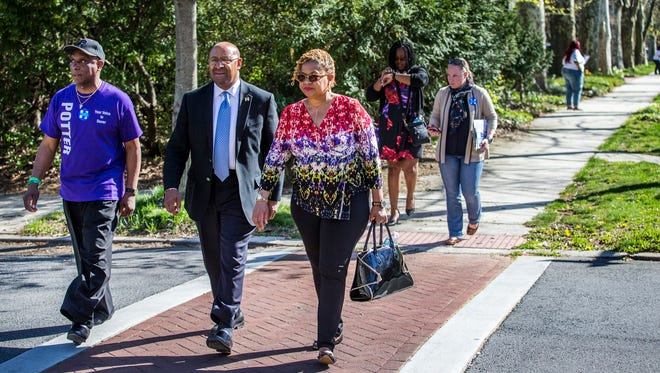 Former Philadelphia Mayor Michael Nutter (center) walks with Rep. Charles Potter Jr. (left), and Councilwoman Hanifa Shabazz (right) while canvassing for Hillary Clinton in Wilmington on Sunday afternoon.