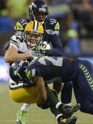 Green Bay Packers receiver Jordy Nelson (87) gets sandwiched against the Seattle Seahawks at CenturyLink Field in Seattle, Wash., on Thursday, Sept. 4, 2014.