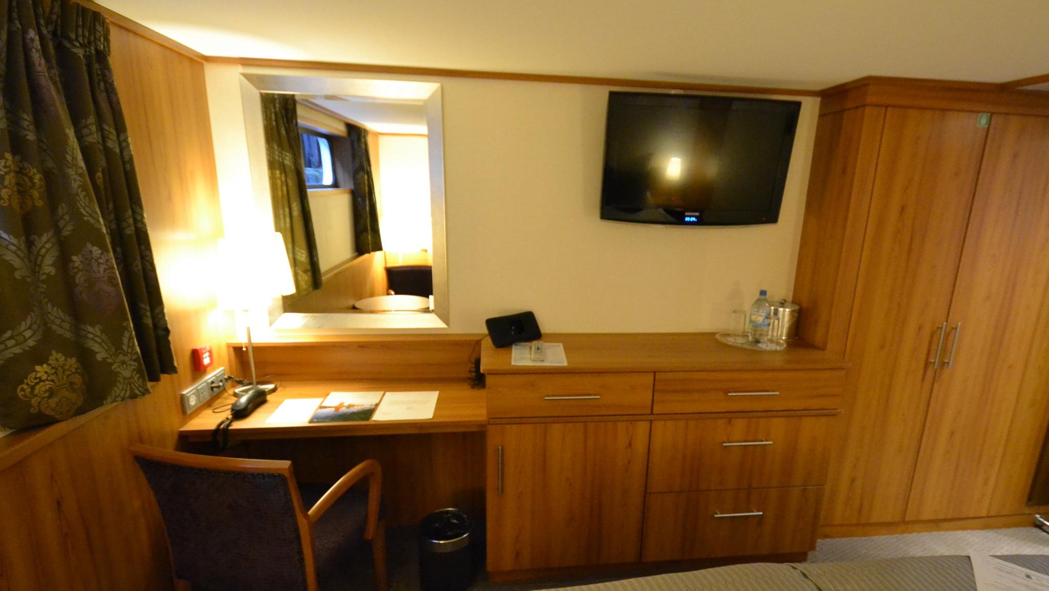 Standard cabins have desk areas, a chair, and flat-screen TVs, among other amenities.