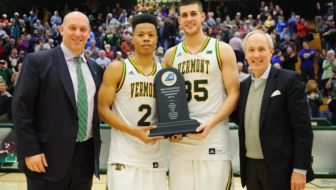 Vermont's Trae Bell-Haynes (2) and Payton Henson (35) pose with the America East regular season trophy with Athletic Director Jeff Schulman (left) and president Tom Sullivan during the men's basketball game between the Binghamton Bearcats and the Vermont Catamounts at Patrick Gym on Wednesday night February 21, 2018 in Burlington. (BRIAN JENKINS/for the FREE PRESS)