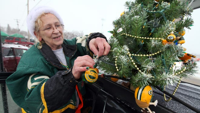 Kristy Roth of Wittenberg decorates her Christmas tree, perched on top of her car, before the Packers played the Pittsburgh Steelers at Lambeau Field on Dec. 22, 2013.
