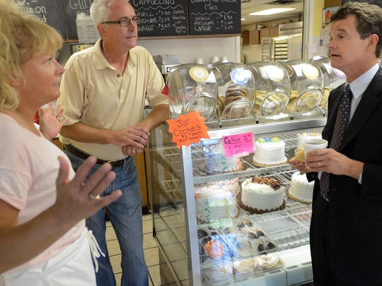 Congressman Dave Trott, right, talks with Milford Baking Company owners Heidi and Mike Kirchner during an Aug. 19 visit to the village.