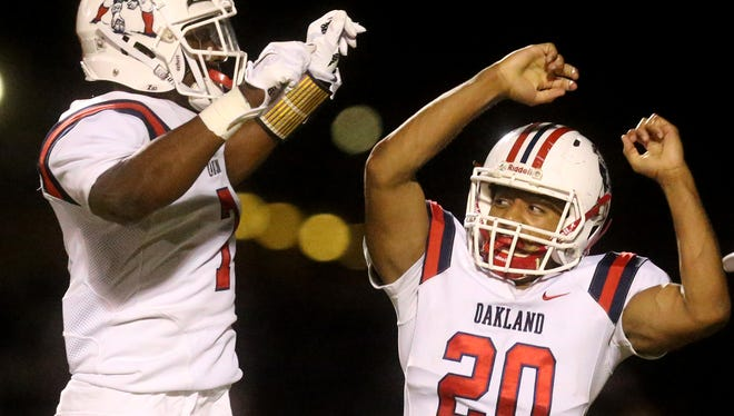 Oakland's Brandon Turner (20) and Jacoby Stevens (7) celebrate Turner's fumble recovery during the game against Riverdale on Friday, Oct. 14, 2016, at Riverdale.