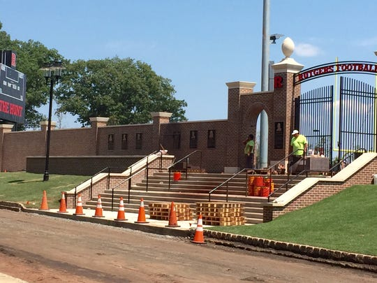 Construction workers finish the entrance to the new Marco Battaglia Practice Complex outside High Point Solutions Stadium at Rutgers.