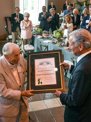 Col. Ben Skardon, left, accepts the Order of the Palmetto from Gov. Henry McMaster, right, during a 100th birthday celebration for him at the Brooks Center in Clemson on Friday, August 11. Skardon also was presented proclamations from the City of Clemson, and the South Carolina Senate. U.S. Rep. Jeff Duncan gave Skardon a flag flown over the Capitol.