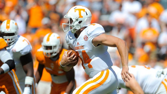 Justin Worley (14) scrambles as the University of Tennessee plays in the Orange and White game at Neyland Stadium. Saturday April 12, 2014, in Knoxville, TN.