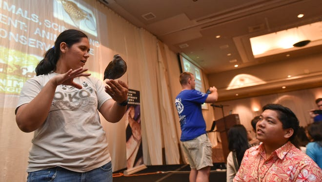 Laura Duenas, Guam Department of Agriculture's Division of Aquatic and Wildlife Resources biologist, handles a ko'ko' bird during a Walt Disney and Dr. Shieh's Clinic sponsored educational outreach at the Hyatt Regency Guam in Tumon on May 9.