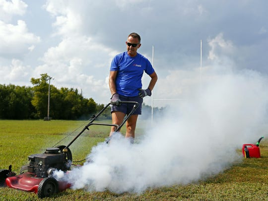 Springfield Rugby Club head coach John Walkman stares at his barely working lawn mower while trying to cut the grass at the club's pitch in Springfield, Mo. on Sept. 4, 2015.