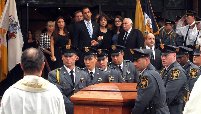 The family of former Morris County Sheriff John M. Fox looks on as his casket is taken from St. Christopher R.C. Church in Parsippany after funeral services. Fox served as County Sheriff from 1975 through 1992. September 30, 2015, Parsippany, NJ.