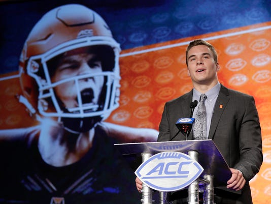 FILE - In this July 13, 2017, file photo, Syracuse's Eric Dungey speaks to the media during the Atlantic Coast Conference NCAA college football media day in Charlotte, N.C. Syracuse quarterback Eric Dungey and cousin Ryan, a motocross champion, share a toughness that's in the family genes. Ryan figures he's broke at least 10 bones racing and Eric has excelled at Syracuse despite at least one concussion. (AP Photo/Chuck Burton, File)