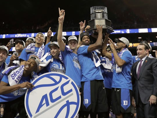 Duke players hold up the championship trophy after