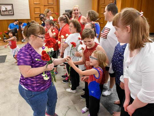 Allie Perkins (left) hands out flowers to the dancers participating in the fourth annual SMILE on Down Syndrome dance recital at the Deaconess Health Science Building Wednesday, August 17, 2016.