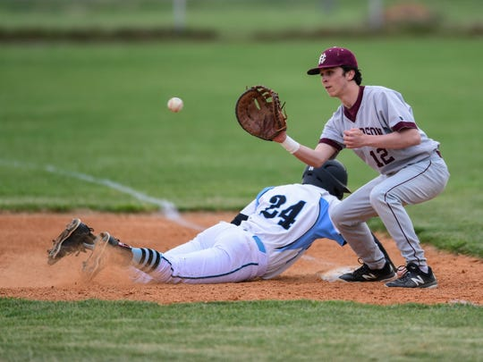 Union County's Coy Burns (24) slides into first base during a pick-off attempt made by Henderson County's Bryce Willett (12) and Henderson Pitcher Dylan Sutton (24), not pictured, at Union County High School in Morganfield, Ky.,, Monday, April 9, 2018. The Colonels defeated the Braves, 6-1.
