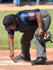 Umpire Janet Moreno Mendinueta sweeps home plate between plays during Penn State's game against Ciego De Avila on Wednesday.