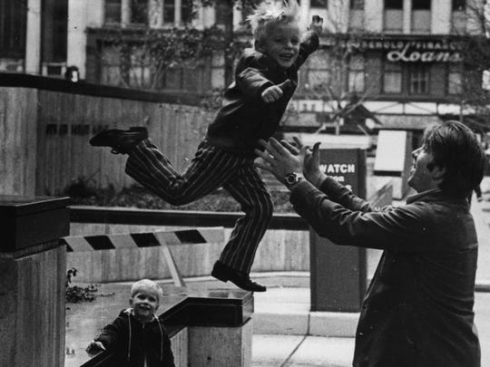 In this Dec. 27, 1971 photo taken at Fountain Square, 4-year-old Gary Walls jumps into the arms of his father, Terry Walls, as Terry Jr., 3, looks on.