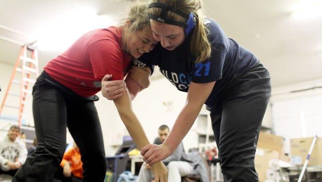 Morgan Huff, 17, wrestles Courtney Lillich, 15, on Dec. 22 in Goshen, Ohio. Huff is the only female on Goshen High School's wrestling team. She practices six days a week and uses her dad's shop two nights of the week because many wrestling facilities do not allow females to wrestle males.