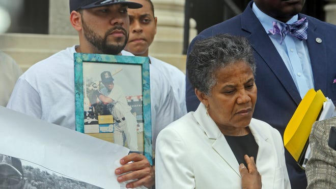 Maria Tolentino, the sister of Dario Francisco Tena, took part in a press conference outside the Federal Courthouse in White Plains on Tuesday to announce a federal lawsuit against the City of Yonkers for the drug raid that led to his death in March 2014. Behind her, Maximo Reyes, a friend, holds a photograph of Tena. Tena died in a fall from a third-floor window. The suit alleges that the death was the result of an illegal police search and the failure of city officials to properly supervise the police department.