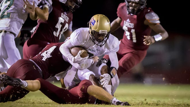 Chandler Basha's Jaylyn Goodman (8) is brought down by middle linebacker Mack Klafter (17)  and outside linebacker Jacob Porter (54) of Red Mountain in the first half of the high school football game at Red Mountain High School on Friday, September 9, 2016, in Mesa.