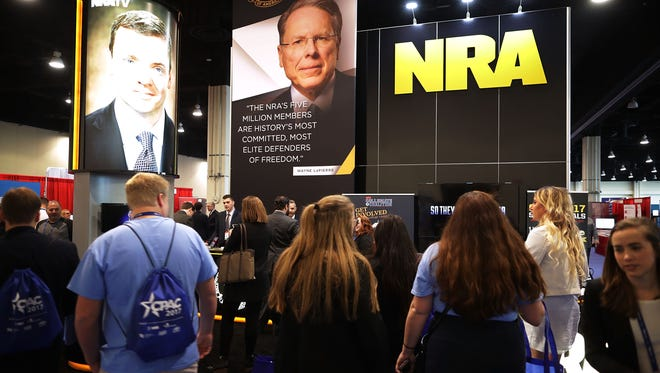 National Rifle Association CEO Wayne LaPierre's image floats above the NRA booth  during the first day of the Conservative Political Action Conference.