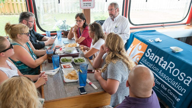 Bill Vincent, Florida Education Association regional specialist, top right, discusses the voting results during a gathering of Santa Rosa County teachers at Johnny Huston's Grille & Bar in Navarre on Tuesday, July 25, 2017.  The Santa Rosa Professional Educators union defeated the Santa Rosa Education Association union by a vote of 52 percent to 43 percent.