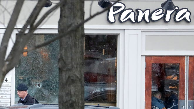 A hole is seen on a glass panel as a man leaves a Panera Bread restaurant in Princeton, where an armed man was holed up across the street from Princeton University's campus on Tuesday, March 20.