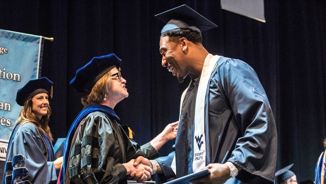 Bruce Irvin, right, receives his degree from Dean Gypsy Denzine during the College of Education and Human Services Commencement at West Virginia University in Morgantown. When Irvin got a multimillion signing bonus after being a first-round draft pick in 2012, the idea of getting his college degree was the last thing on his mind. But after having a son, the former high school dropout made getting that degree a priority and was one of many NFL players this offseason who got to don a cap and gown instead of a helmet.