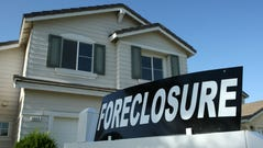 A foreclosure sign sits in front of a home for sale