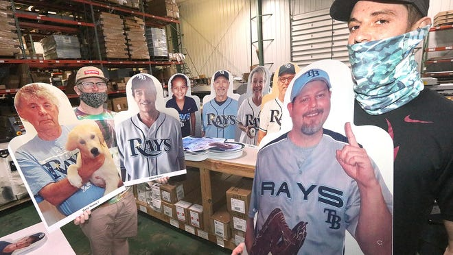 """Tyler Reyno, at right, and Kyle Coyle, print production specialists at DME Visual in Daytona Beach, display some of the hundreds of Tampa Bay Rays fan cutouts the company has produced for the team. Reyno pitched the company's services to the Rays after seeing fan cutouts at other stadiums on TV. """"I thought, 'I really should give them a shout-out here and see if we could do it for them,'"""" Reyno said. """"And it worked out."""""""